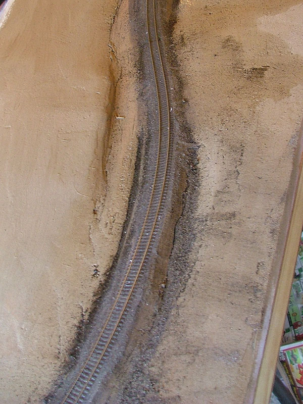This is the track in the midst of ballasting. It has received it's first layer of stone and has been glued.
